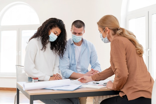 Female realtor with medical mask showing couple house plans