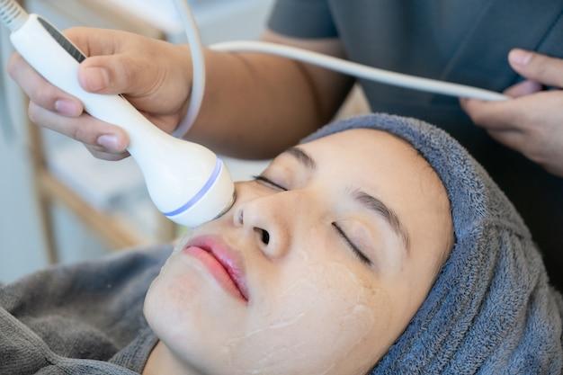 Female receiving anti-aging cosmetics using ultrasound cavitation machine.