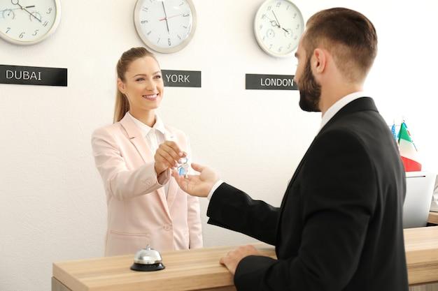 ホテルの顧客に部屋の鍵を渡す女性の受付係