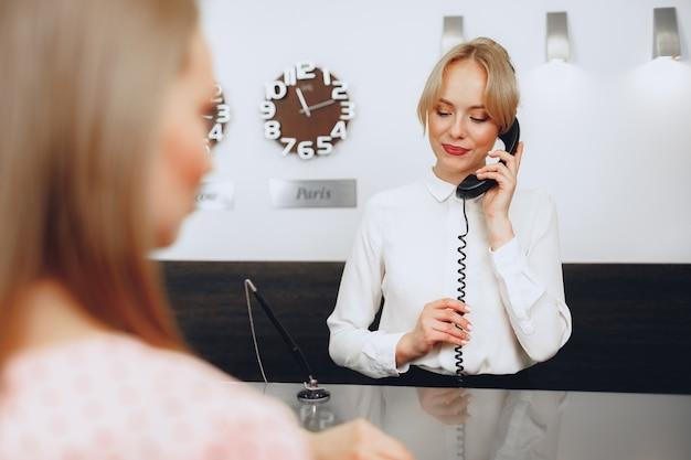 職場で電話で話しているホテルの女性受付係