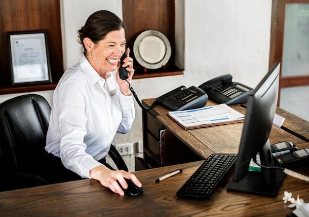 Женский регистратор, работающий на стойке регистрации