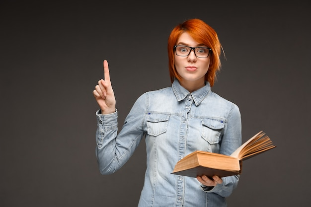 Female redhead student hold book, found solution