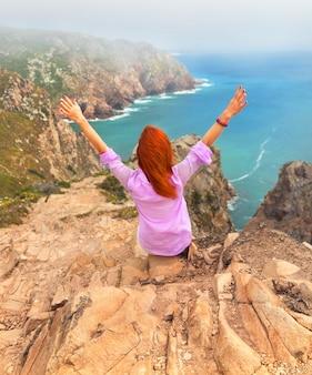大西洋、シントラ、ポルトガルを背景に岬ロカに座っている女性の赤毛の旅行者