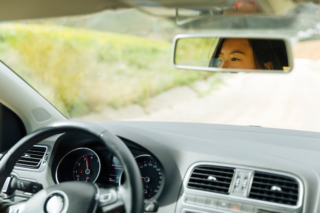 Female reflection in car mirror