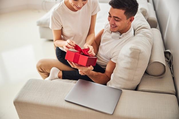 Женщина радуется подарку от супруга-мужчины