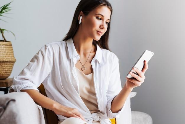 自宅でリラックスし、スマートフォンを使用してテキストメッセージを送信したり、写真を共有したり、友達とコミュニケーションしたり、メールをチェックしたり、動画を見たり、オンラインでゲームをしたりする女性。 web接続されたガジェットでのエンターテインメントの機会。