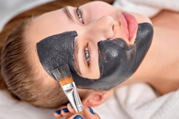 목탄 얼굴 마스크로 편안한 여성, 브러시를 사용하여 여성 고객의 얼굴에 바르는 전문 미용사. 흰색 목욕 가운에 침대에 누워 측면을 보고 여성에 상위 뷰. 아름다움