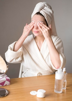 Female removing eye shadow with micellar water