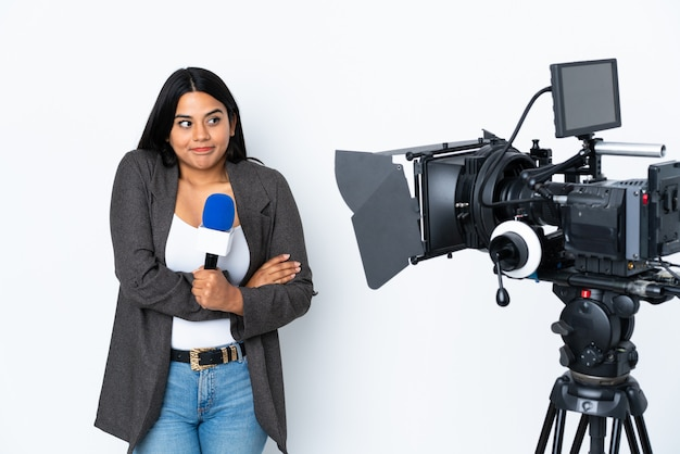 Female reporter holding a microphone and reporting news on white wall making doubts gesture while lifting the shoulders