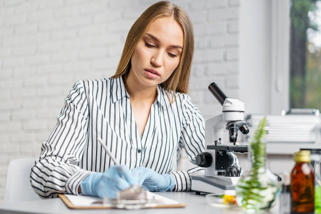 顕微鏡とクリップボードを持った彼女の机の女性研究者