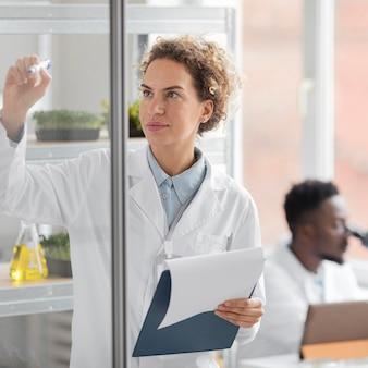 Ricercatore femminile nel laboratorio di biotecnologie con appunti