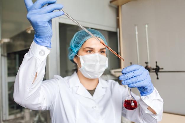 실험실에서 테스트 튜브로 조사를하는 보호 마스크의 여성 연구원