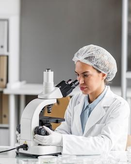 Женский исследователь в лаборатории биотехнологии с микроскопом и копией пространства