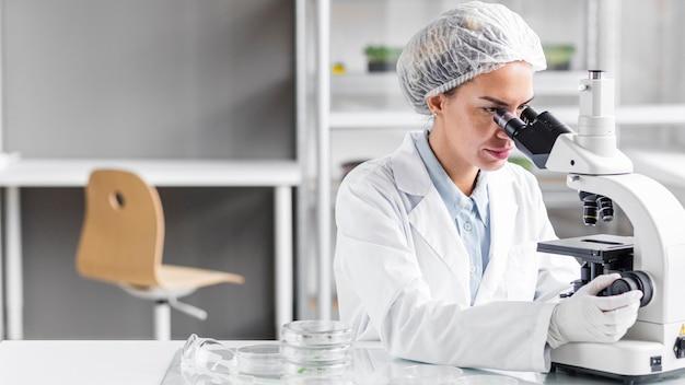 Женский исследователь в лаборатории биотехнологии с микроскопом