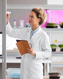 Женский исследователь в лаборатории биотехнологии с планшетом