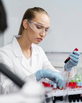 테스트 튜브 및 안전 안경 실험실에서 여성 연구원