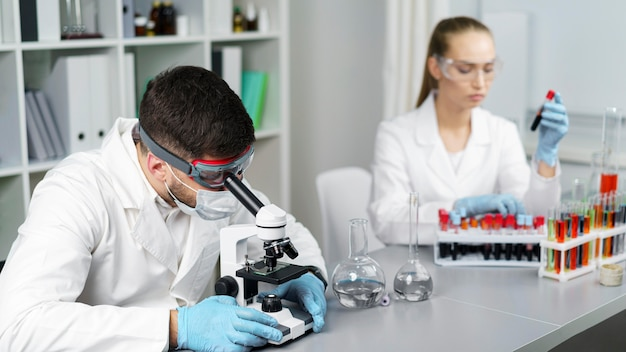 Female researcher and male colleague in the laboratory with test tubes and safety glasses