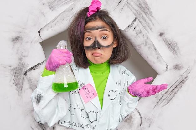 화학 반응을 연구하는 여성 연구원은 시약이 폭발하는 이유를 모르고 실험실 포즈에서 유니폼을 입은 종이 구멍을 통해 신제품을 개발합니다.