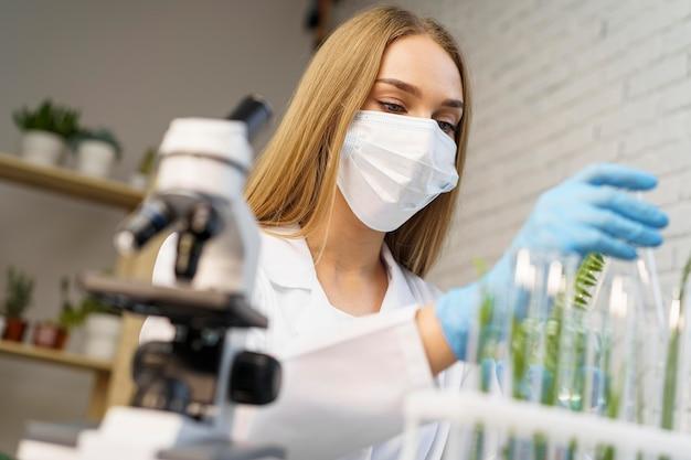 研究室で医療マスクを持つ女性研究者