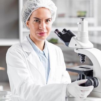 Женщина-исследователь с микроскопом в лаборатории биотехнологии