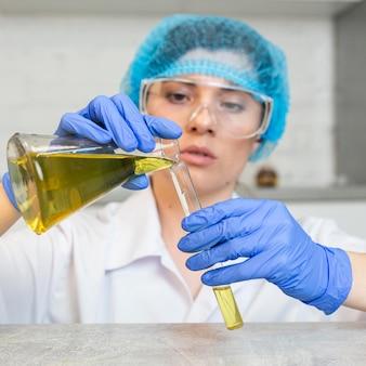 과학 실험을하는 안전 안경과 머리 그물을 가진 여성 연구원