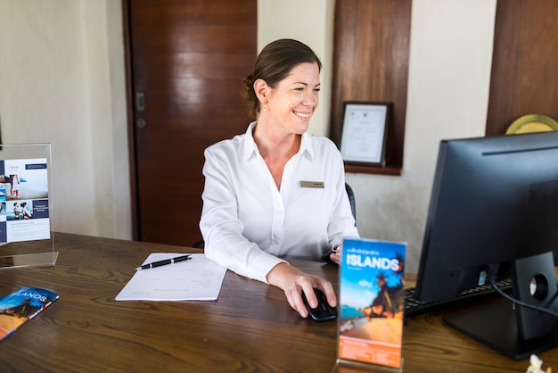 Female resort receptionist working on a computer