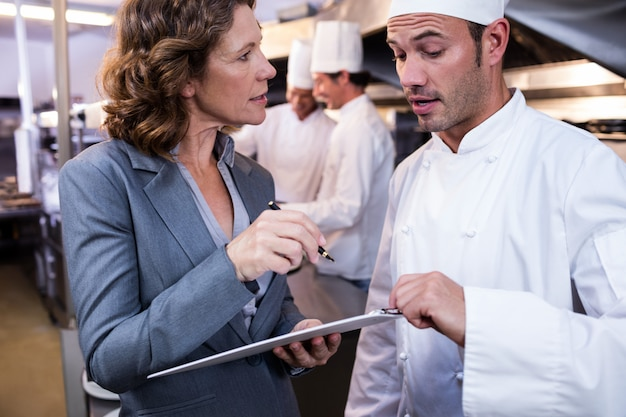 Female restaurant manager writing on clipboard while interacting to head chef