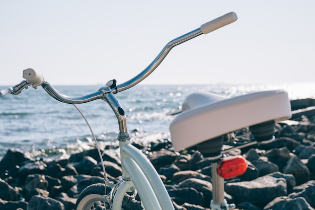 Female retro bicycle on the beach with blue sea on sunny day