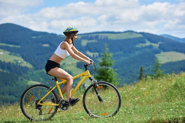 Женский всадник на велосипеде на желтом велосипеде на сельской тропе в горах в летний день