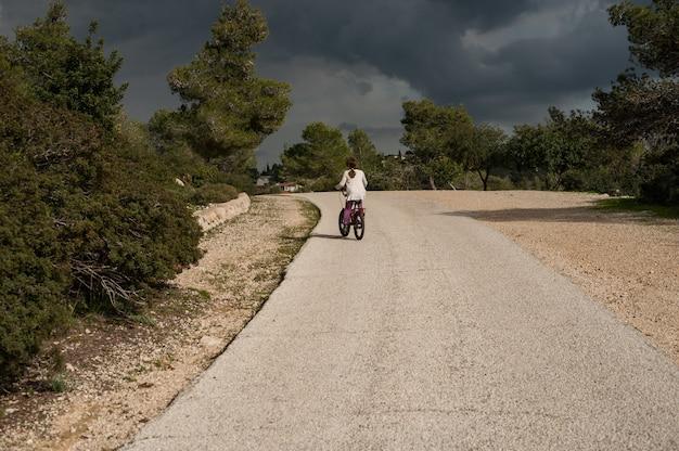Женщина, едущая на велосипеде по дороге в дневное время