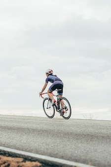 Female road cyclist cycling up the hill