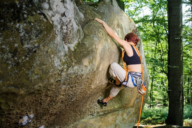 Female rock climber gripping handhold while lead climbing on a large boulder, with rope and carbines