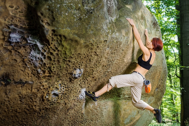 Female rock climber on her challenging way up, bouldering
