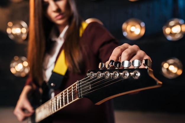 Женский рок-гитарист в костюме настраивает гитару