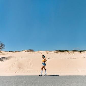 Female in rollers on sandy road