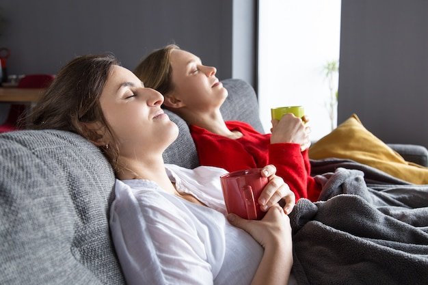 Female roommates having cold and resting at home