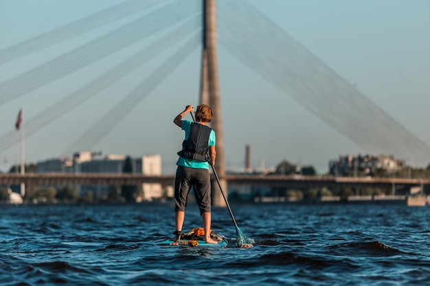 Female rowing with sup paddle boards along the river