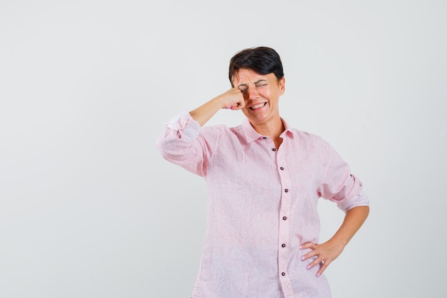 Female rubbing eye while crying in pink shirt and looking offended , front view.