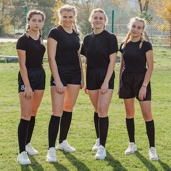Female rugby team looking at photographer
