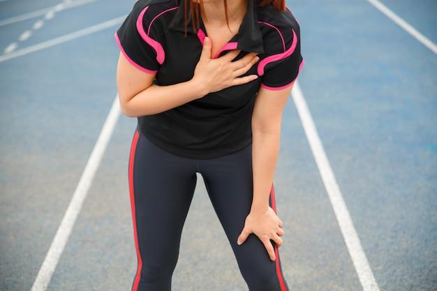 Женский бегун спортсмен травмы груди и боли. женщина страдает от боли в груди или симптомов сердечных заболеваний во время бега по синей прорезиненной беговой дорожке.