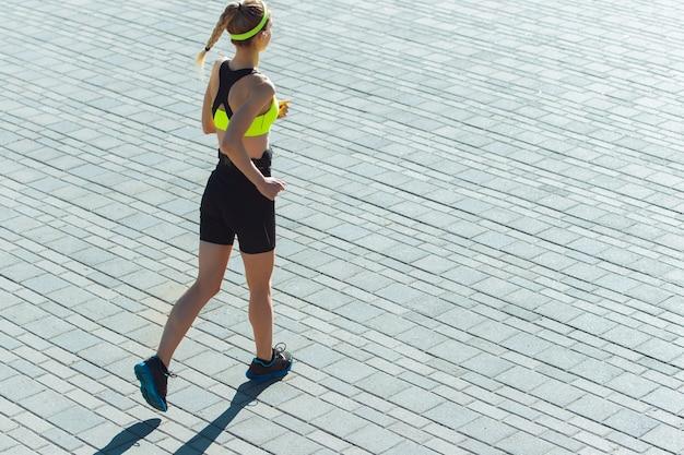 女性ランナー、屋外でのアスリートトレーニング。プロのランナー、路上で運動するジョガー。