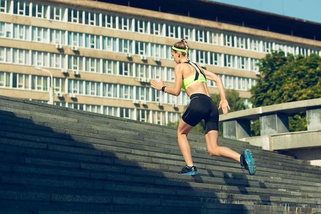 Corridore femminile, atleta che si allena all'aperto nel giorno soleggiato dell'estate.