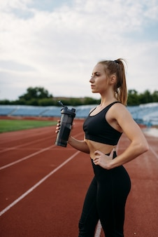 女性ランナーが水を飲み、スタジアムでトレーニング