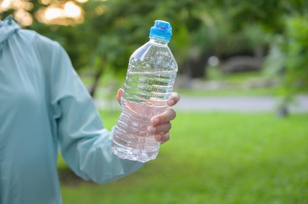 Female runner holding bottle water.