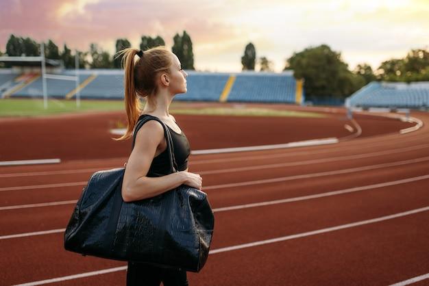 Female runner holds sport bag, training on stadium