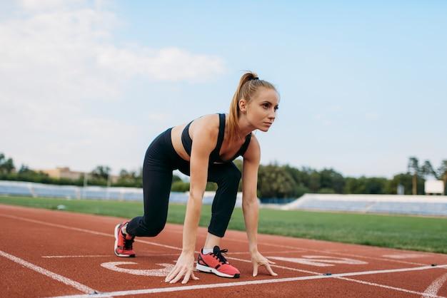 スタートラインでのスポーツウェアの女性ランナー、スタジアムでのトレーニング。屋外アリーナで実行する前にストレッチ運動をしている女性