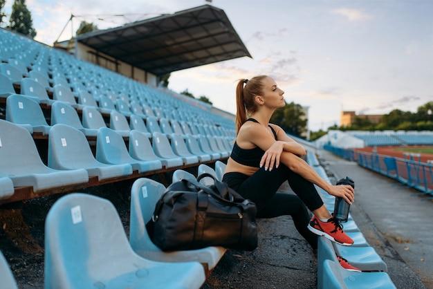 Бегунок в спортивной одежде сидит на трибуне и пьет воду, тренируясь на стадионе. женщина делает упражнения на растяжку перед бегом на открытой арене