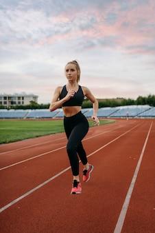 女性ランナーのジョギング、スタジアムでのトレーニング