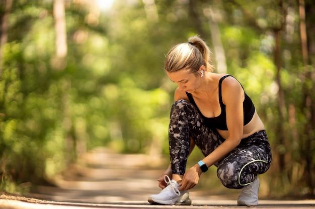 森の小道でスニーカーをひもで締める女性ランナー。