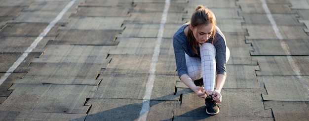 Female runner lacing her sneakers on a stadium running track. healthy lifestyle